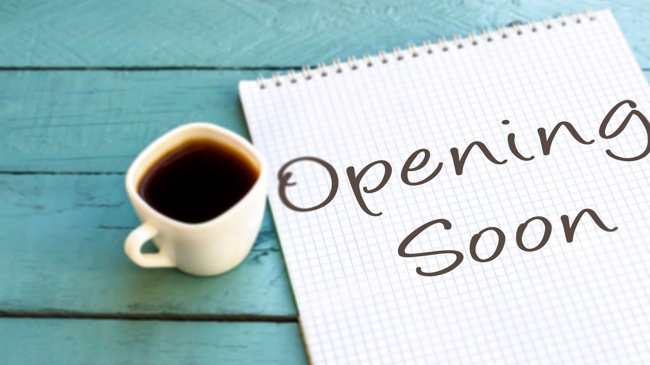 A shop sign next to a cup of coffee saying opening soon, indicating a company back in business on the share market