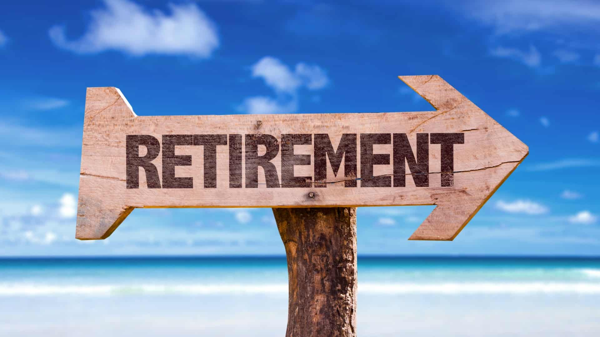 Wooden arrow sign stating 'retirement' against backdrop of beach