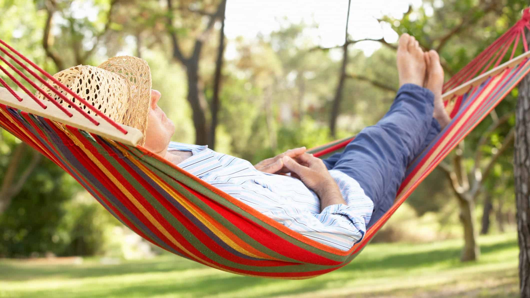 Retired man reclining in hammock with feet up, retire early