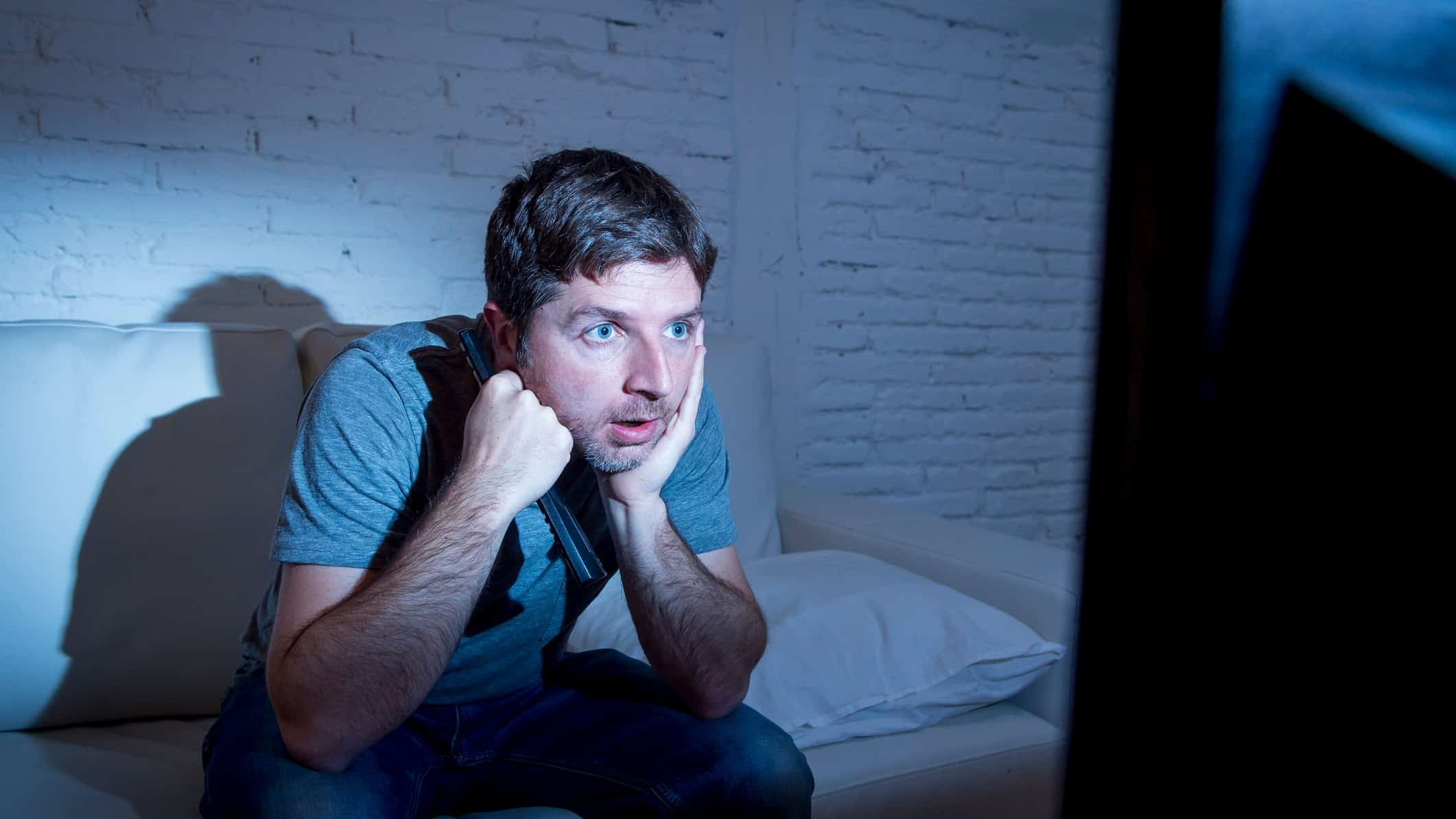man intently watching tv representing media asx share price on watch