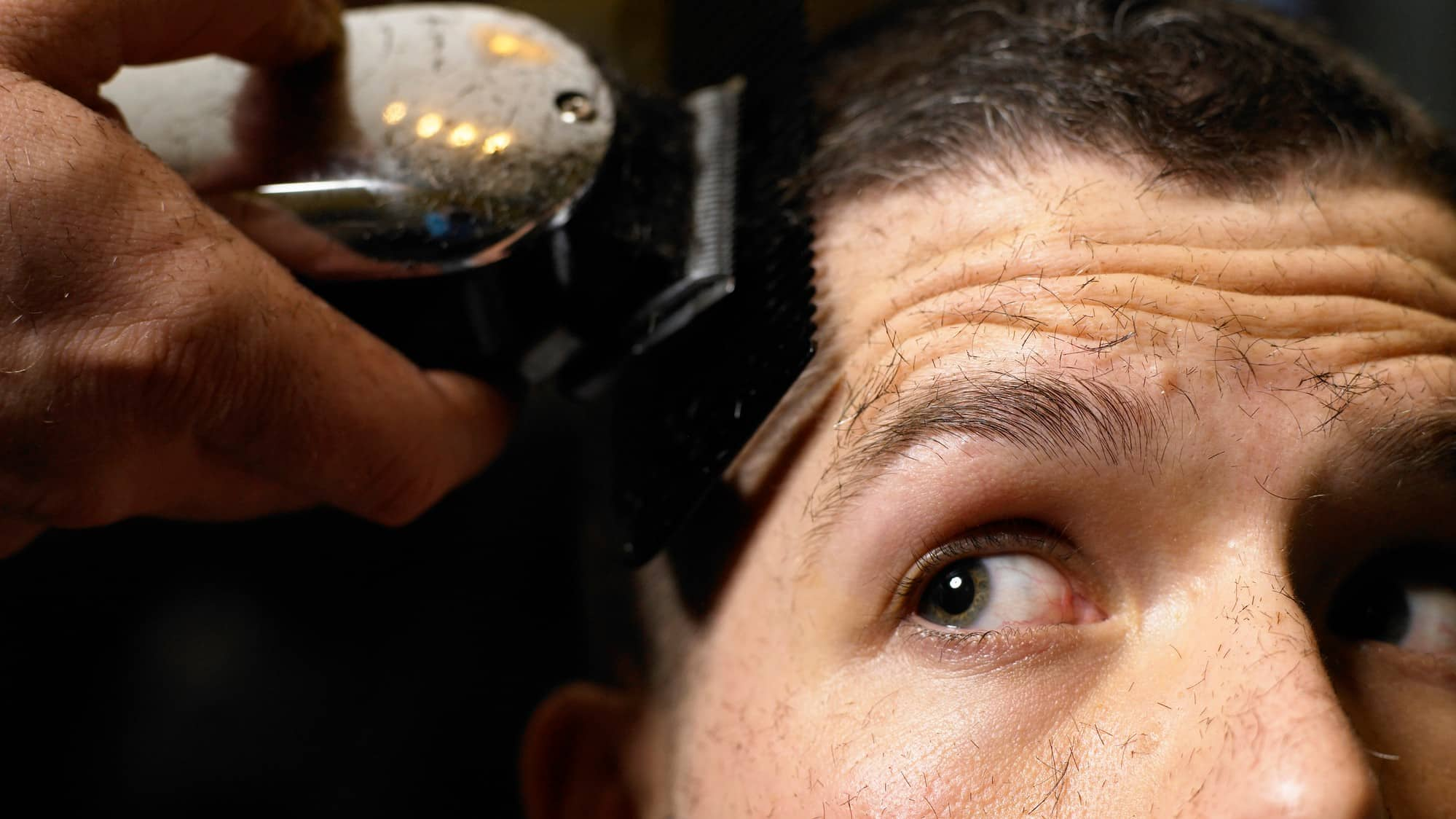 man looking up as if watching asx share price whilst using electric shaver