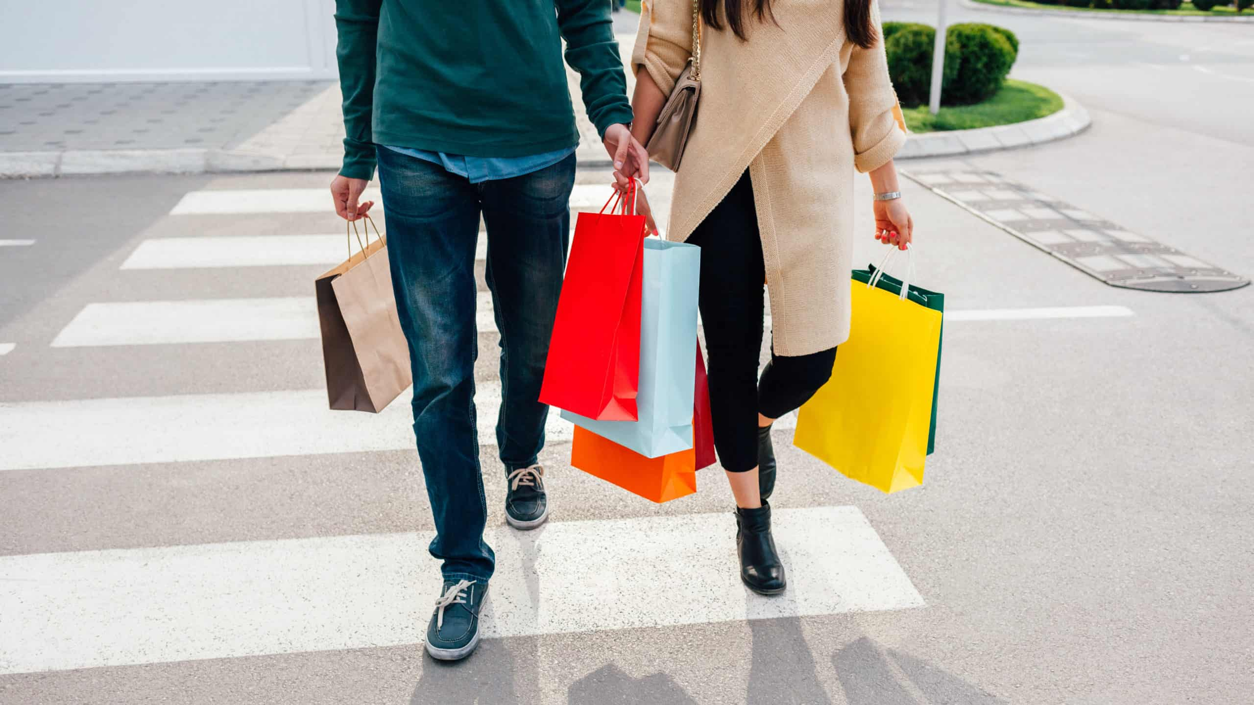 two people walking along carrying shopping bags