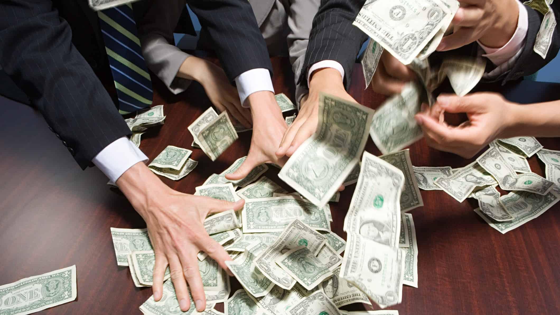 hands all grabbing at cash representing US shares