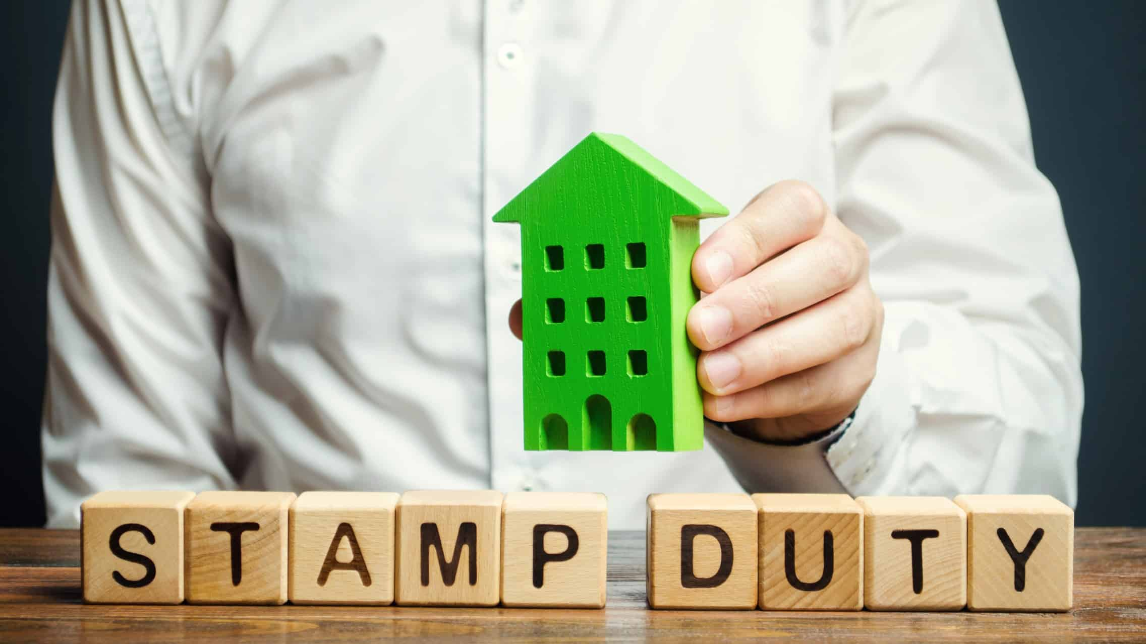 asx investor placing wooden house block on other blocks spelling words stamp duty