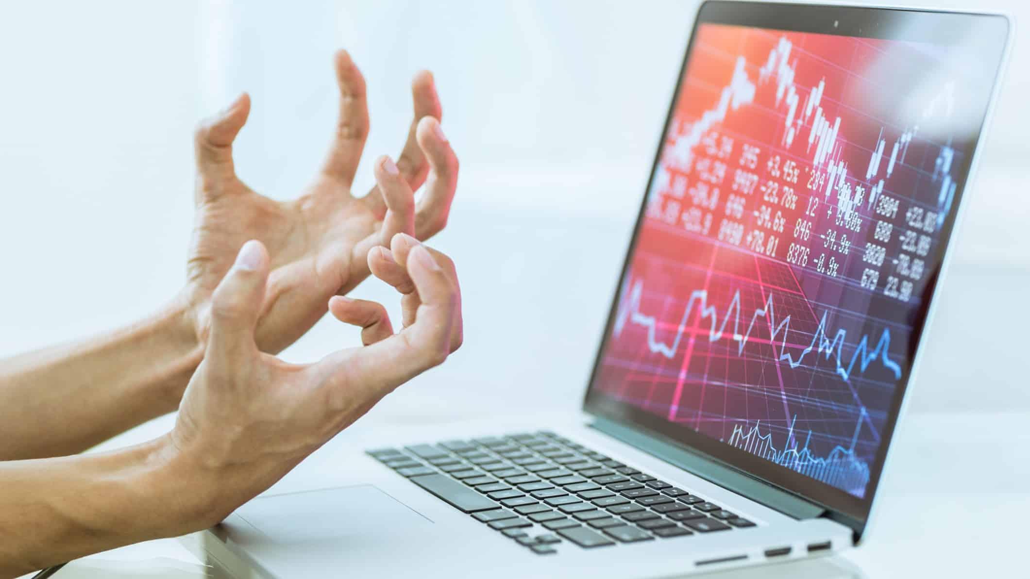 hands making frustrated gesture at computer screen depicting stock market crash charts