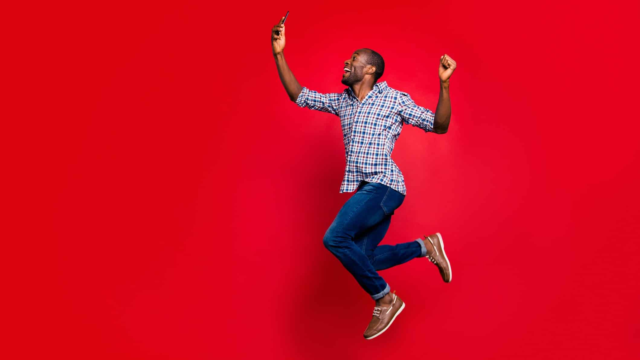 rising telstra share price represented by man jumping in the air for joy looking at mobile phone