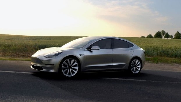 tesla stock represented by tesla electric car driving along country road