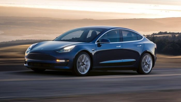 Image of a Tesla vehicle driving along an open road