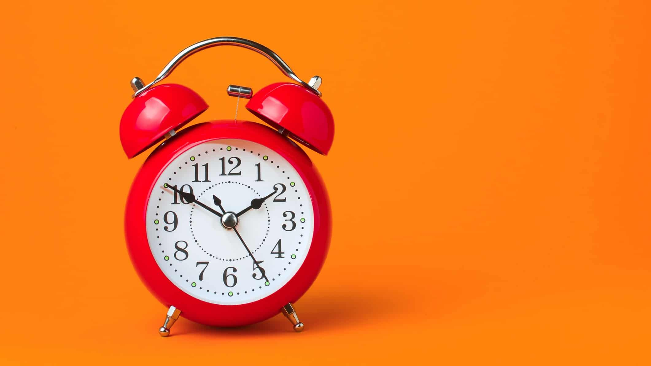 credit corp share price represented by red alarm clock against bright orange background