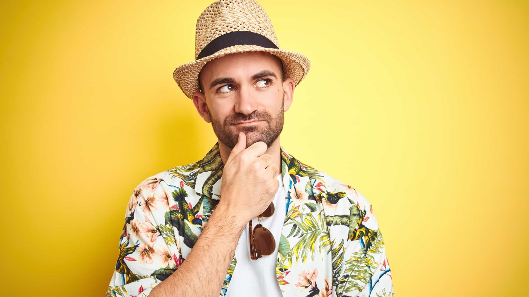 A traveller dressed in colourful shirt and panama hat looking puzzled, indicating uncertainty in the travel share price