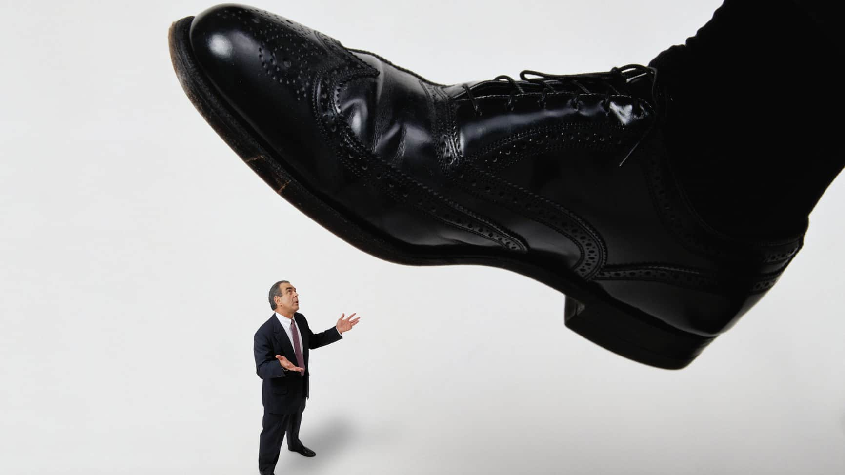 virgin ceo steps down represented by giant shoe about to step on reluctant miniature business man