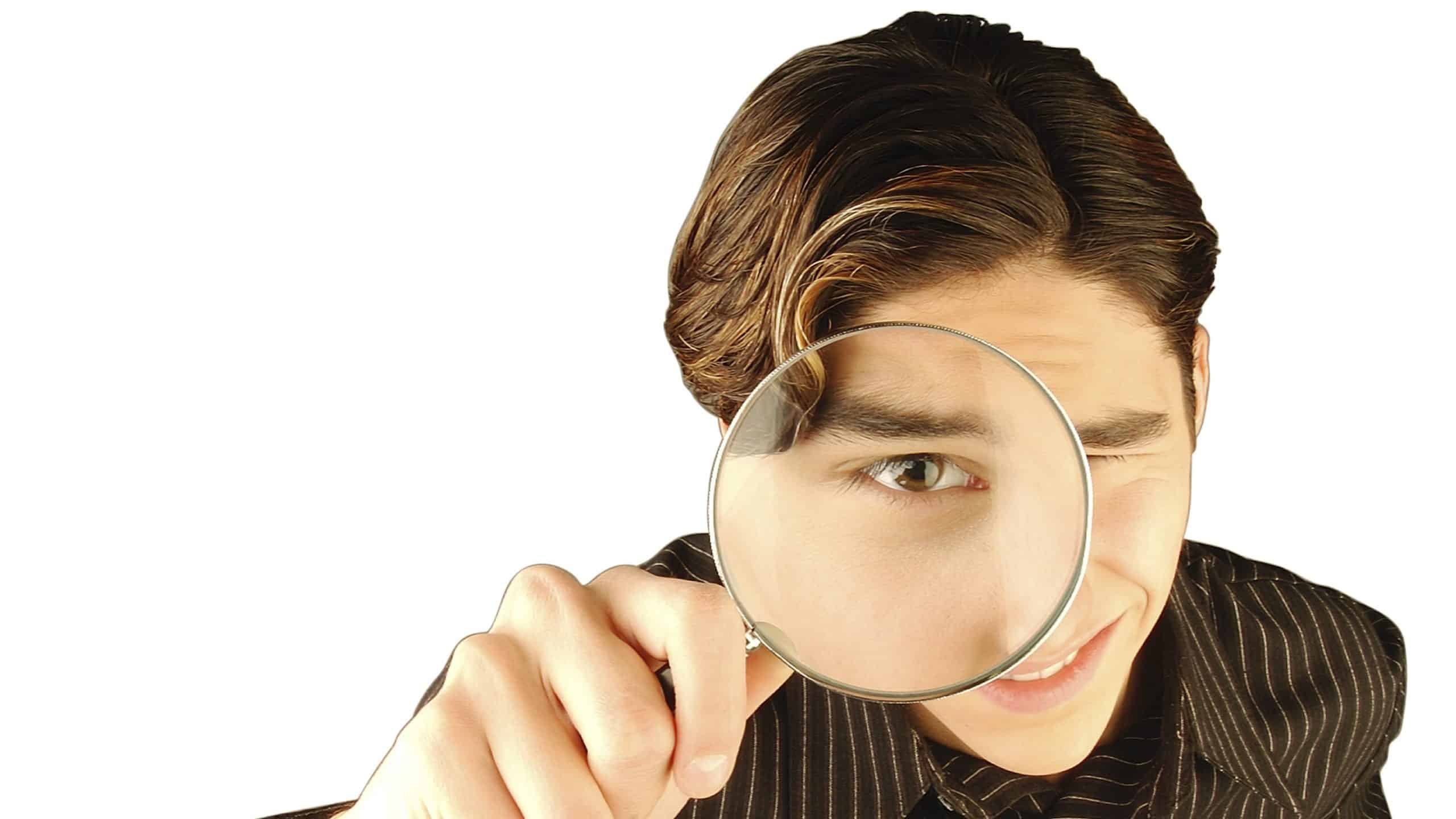 asx share price on watch represented by young man looking intently through magnifying glass
