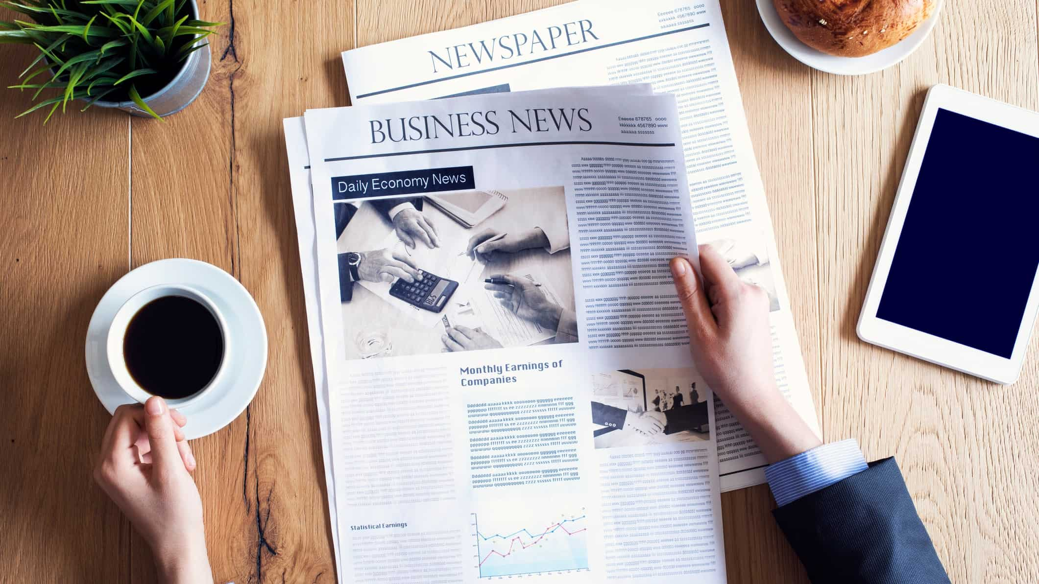 man reading business newspaper with coffee