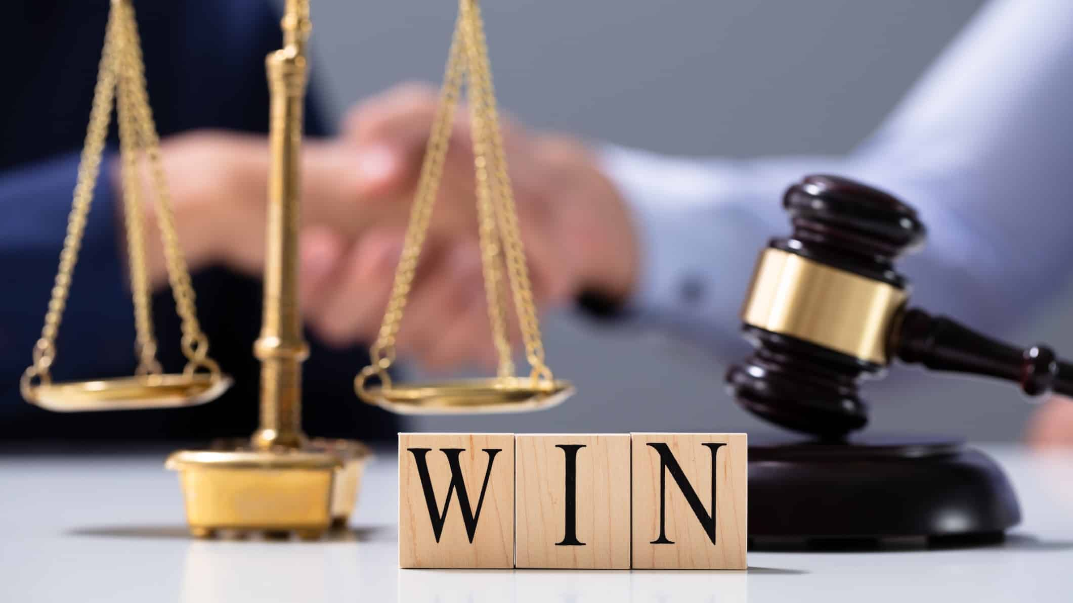 Woolworths win in court represented by scales, judges hammer and wooden blocks spelling the word win