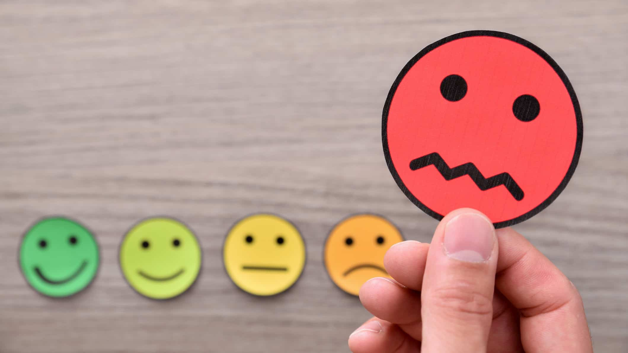 hand selecting unhappy face icon from choice of happy and neutral faces signifying worst performing asx shares