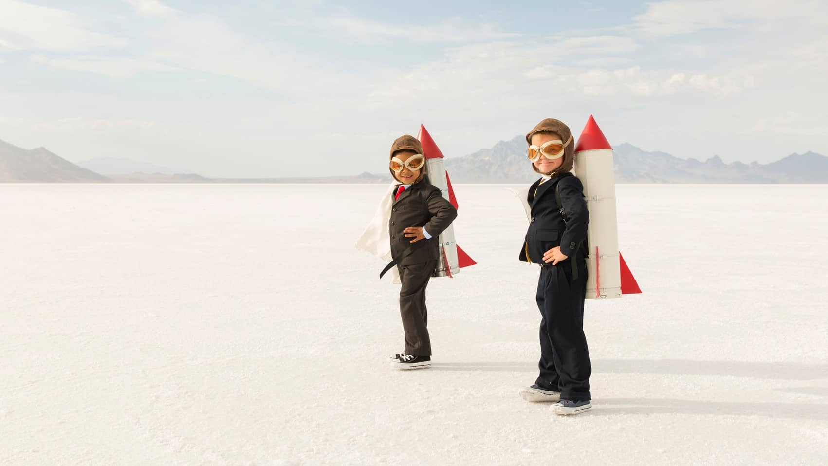 Two boys with cardboard rockets strapped to their backs, indicating two ASX companies with rocketing share prices