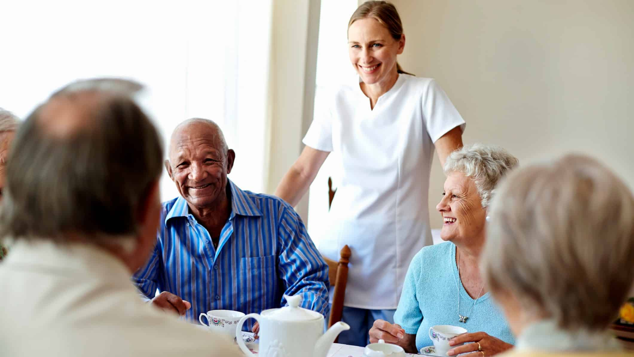 healthcare worker overseeing group of aged care residents at table