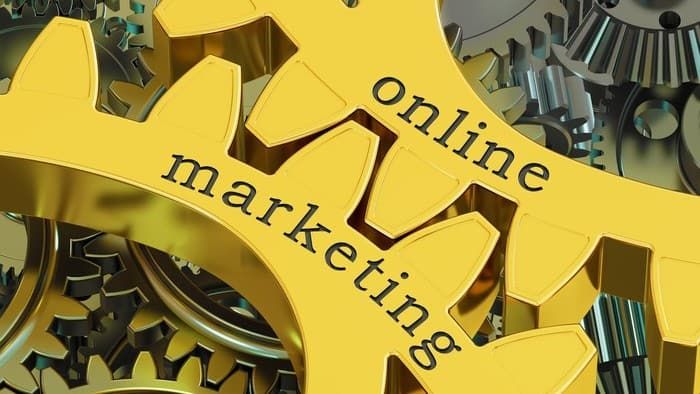 Yellow cogs of a wheel with 'online marketing' written on them in black lettering