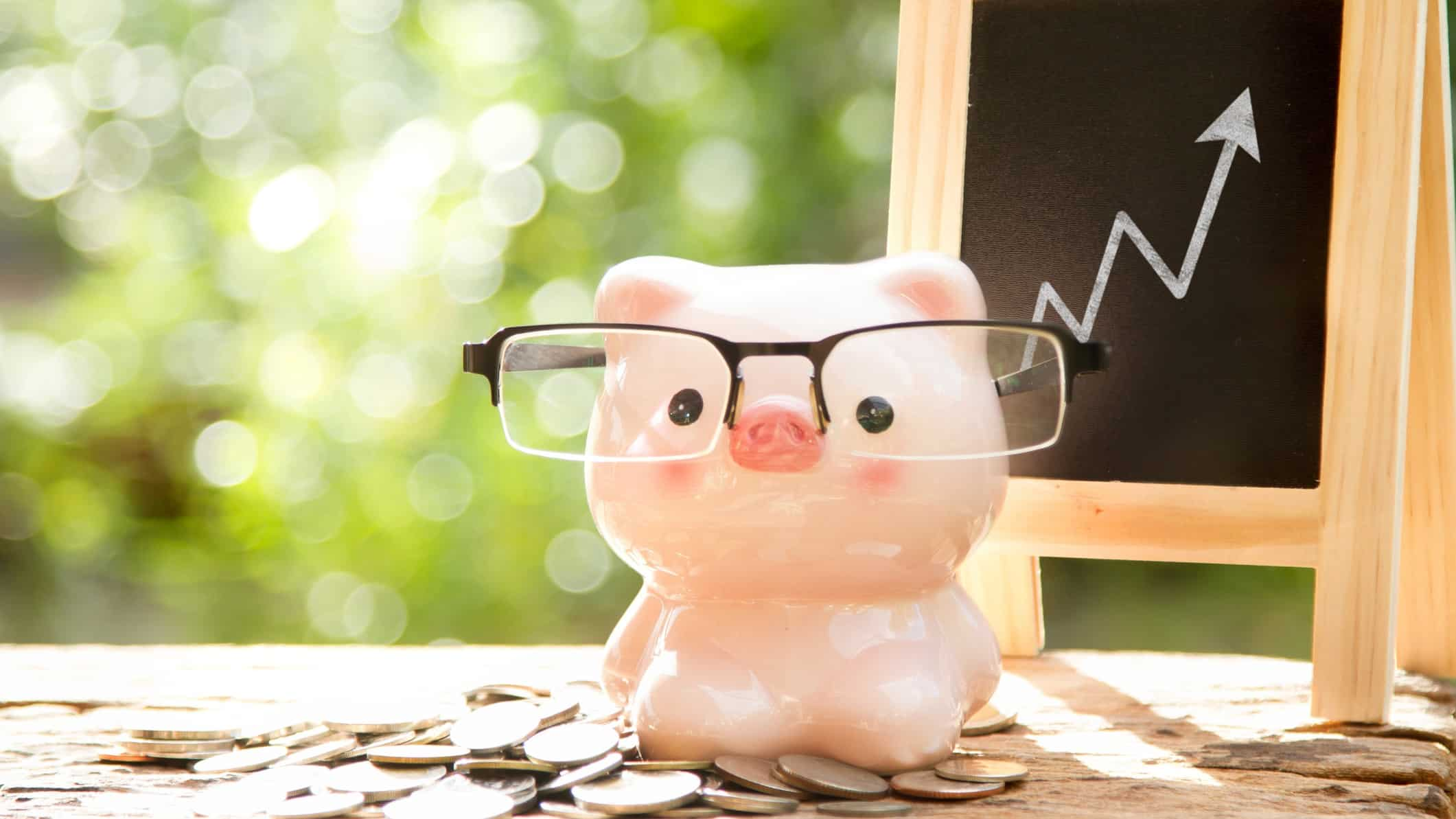 Piggy bank in front of blackboard chart with rising arrow