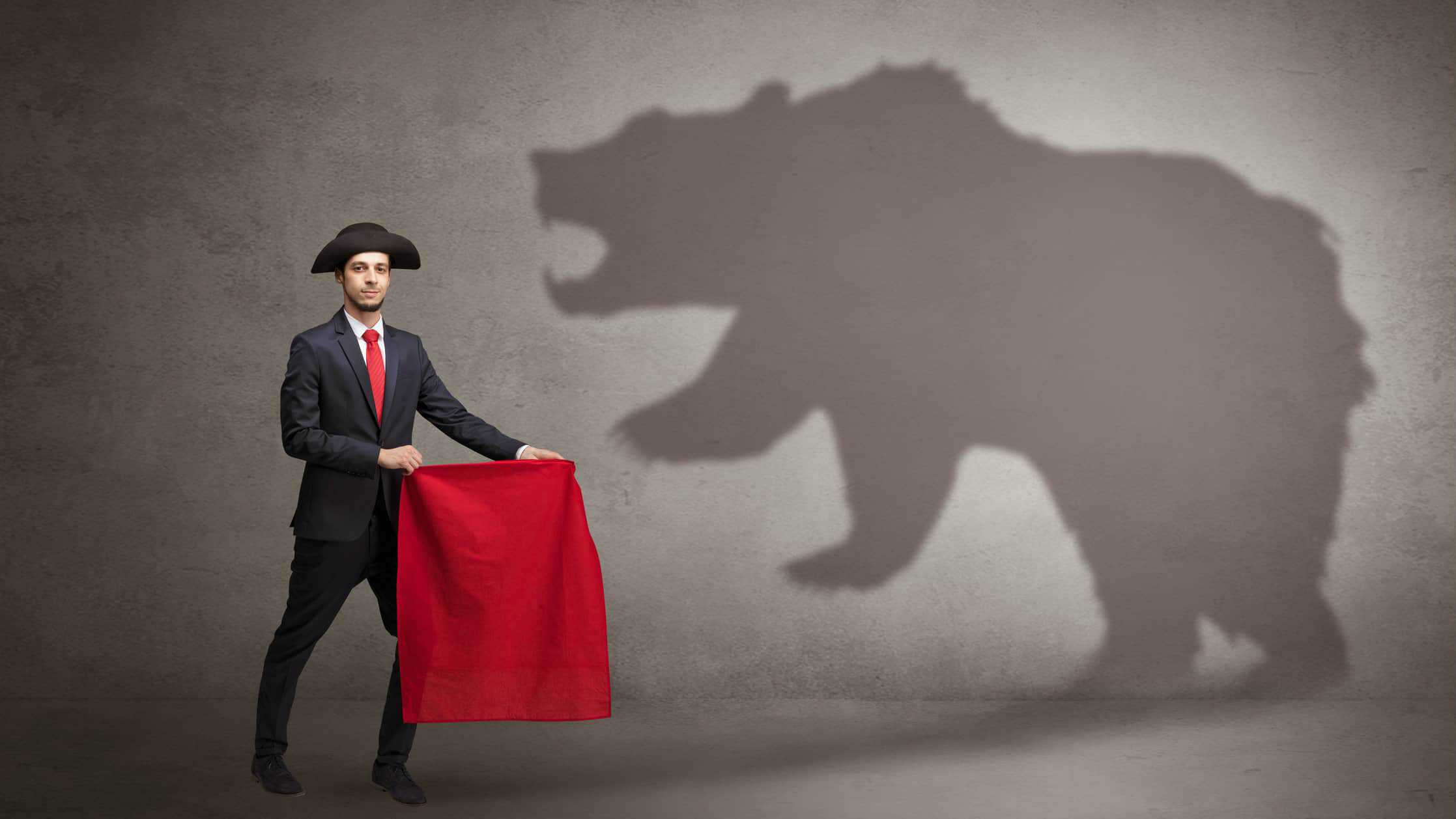Broker holding red flag in front of bear