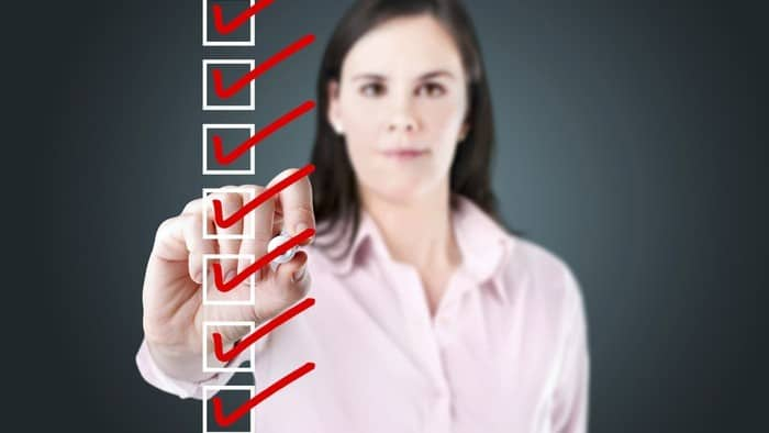 Woman in pink shirt ticks checklist with red checkmarks