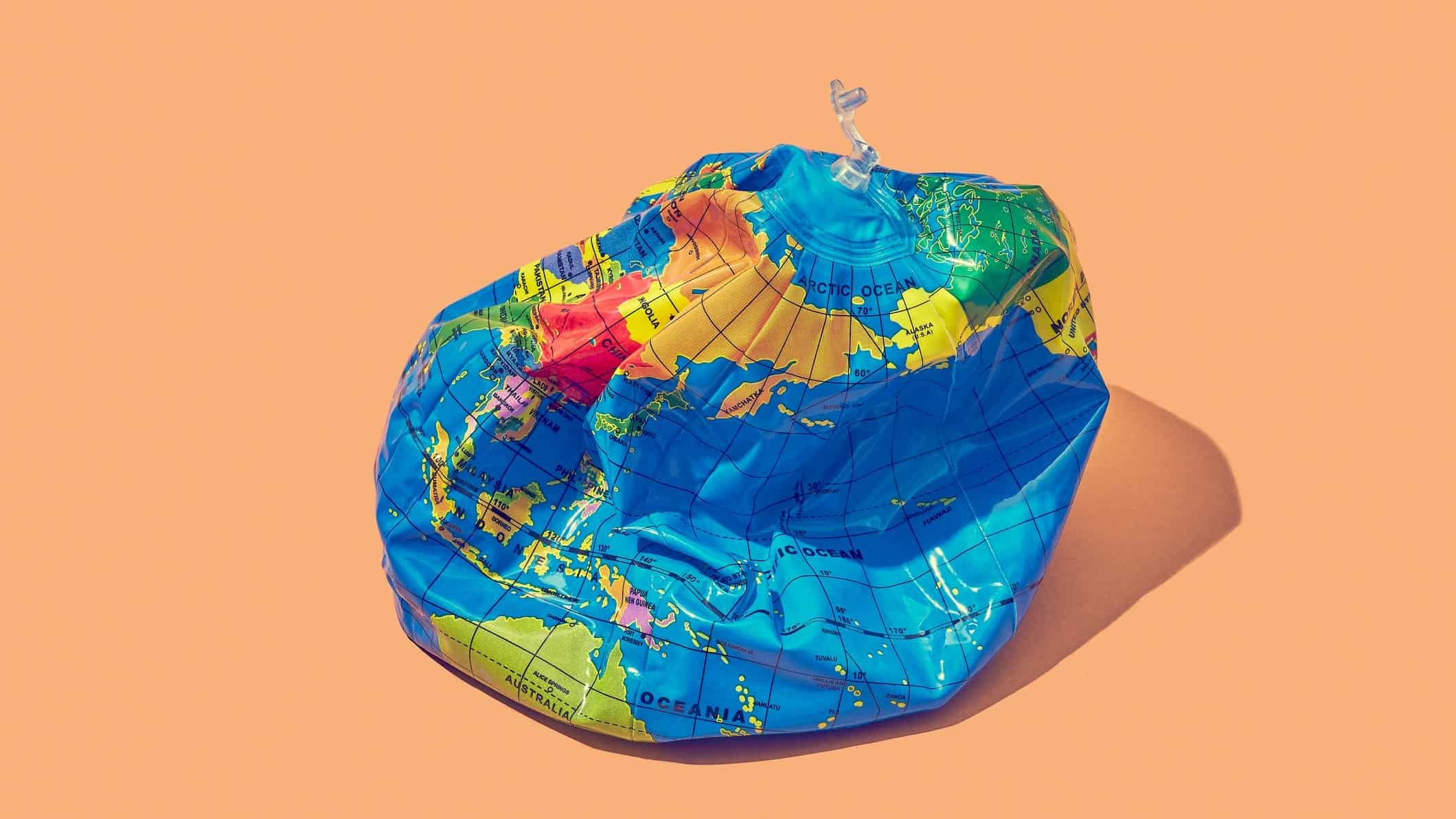 Deflated world globe on peach background to symbolise impact of climate change on the economy