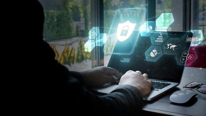 Man on laptop with cybersecurity symbols