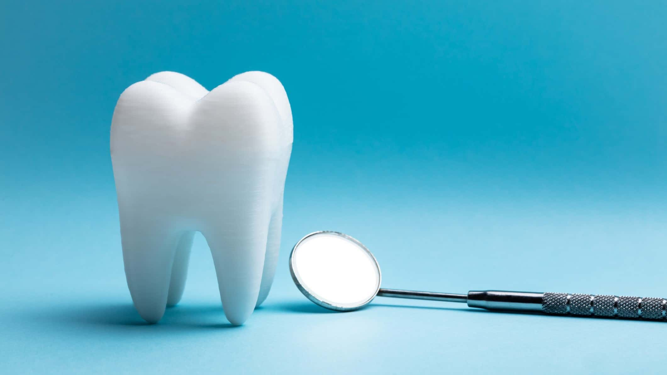 Tooth and dentist tool on blue background