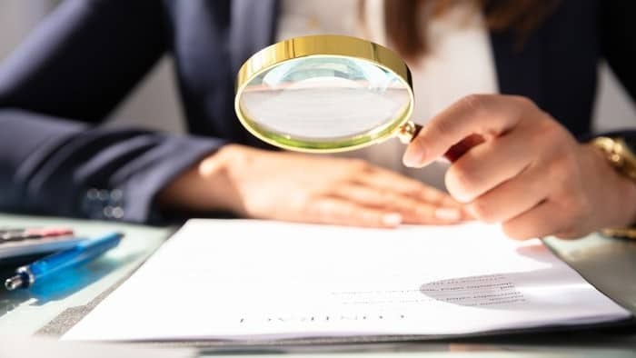 close up of magnifying glass over paperwork