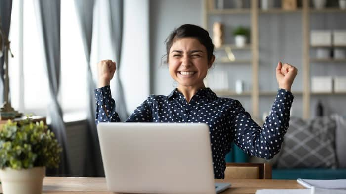 Smiling female investor holds hands up in victory in front of a laptop
