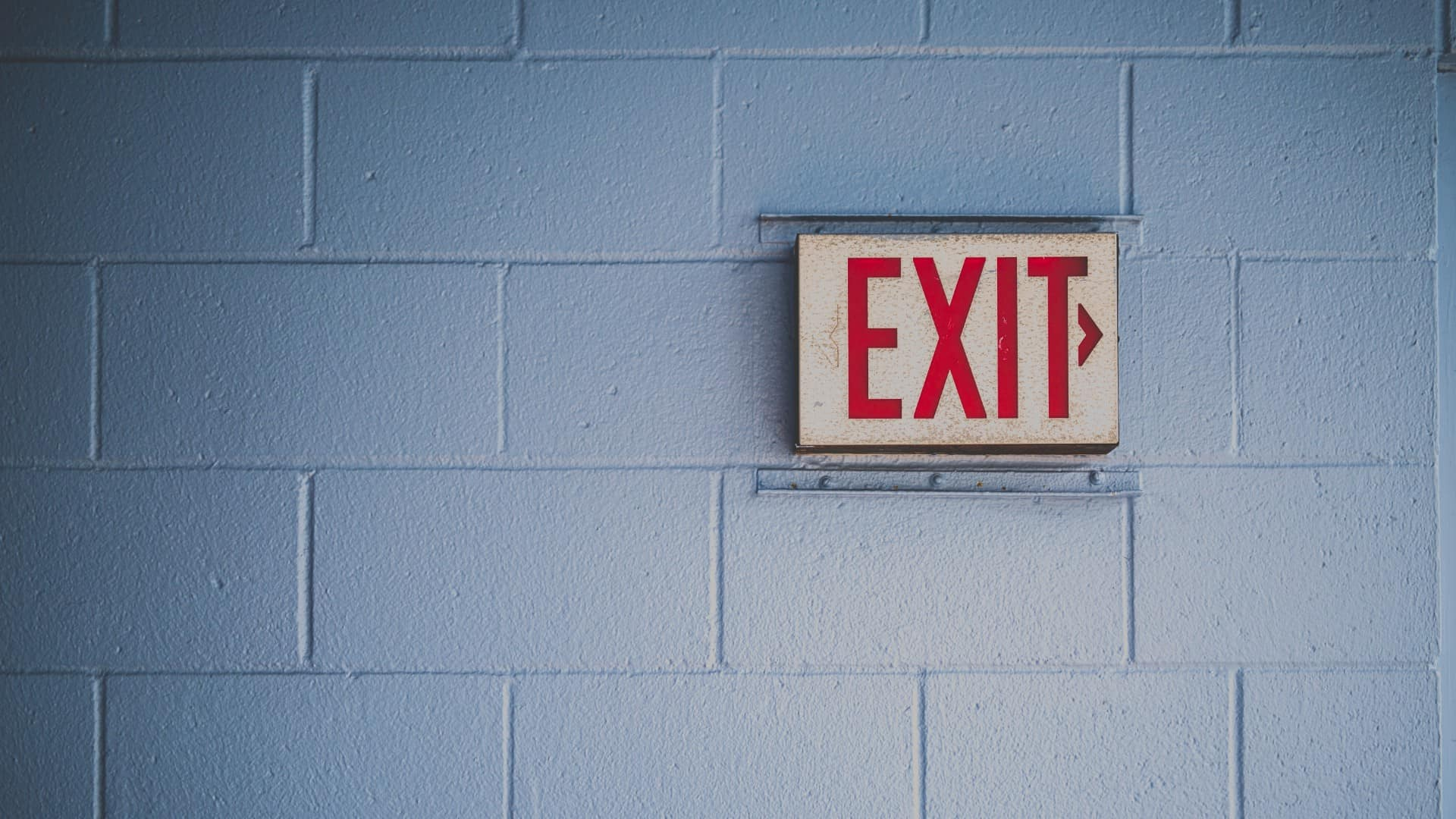 Red exit sign on brick wall