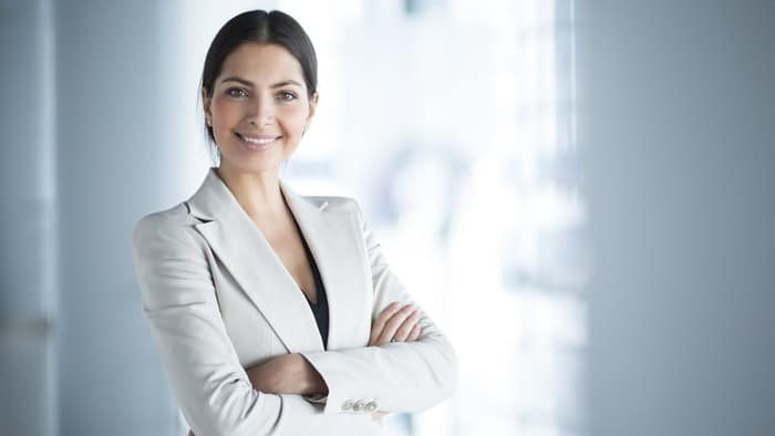 Young female investor in business attire smiling with folded arms