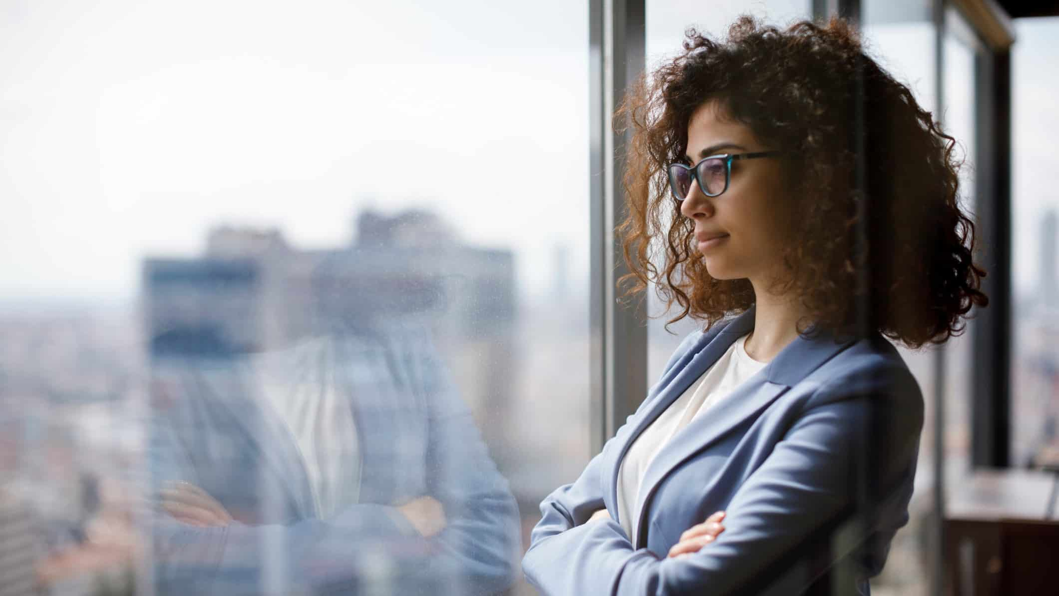 Young Female investor gazes out window at cityscape