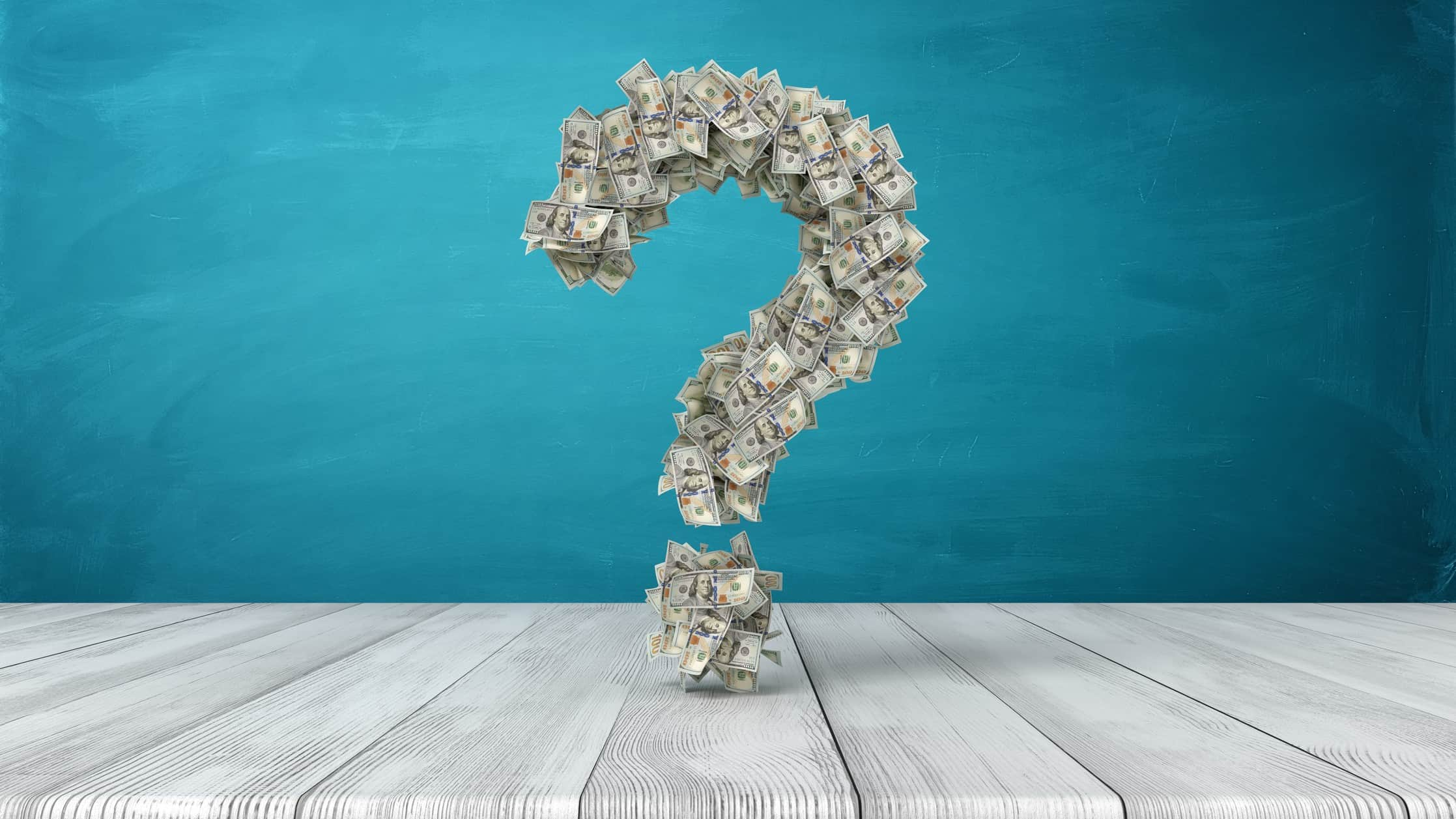 Question mark made up of banknotes in front of blue background