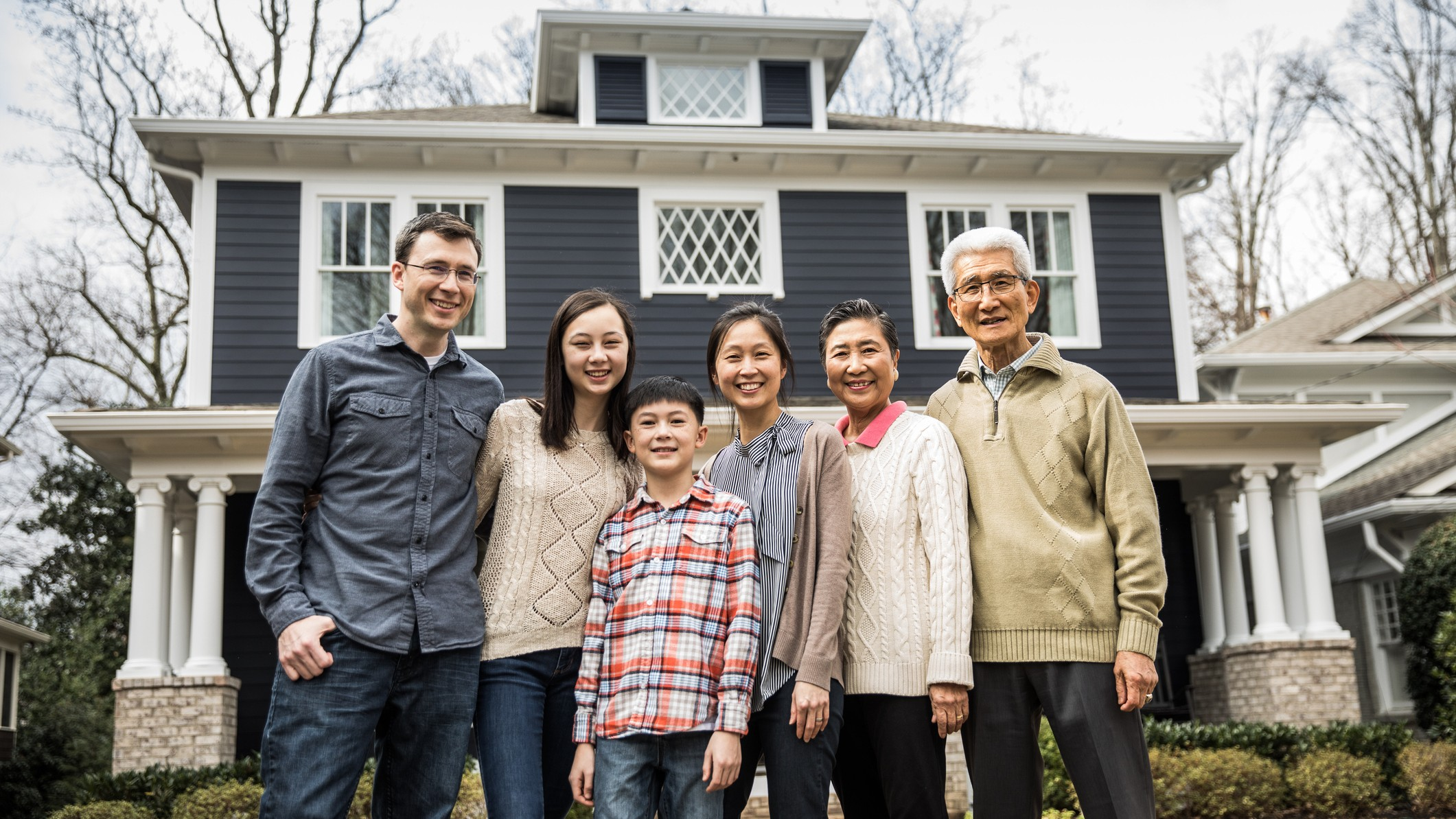 Multiple generations of a family in front of house
