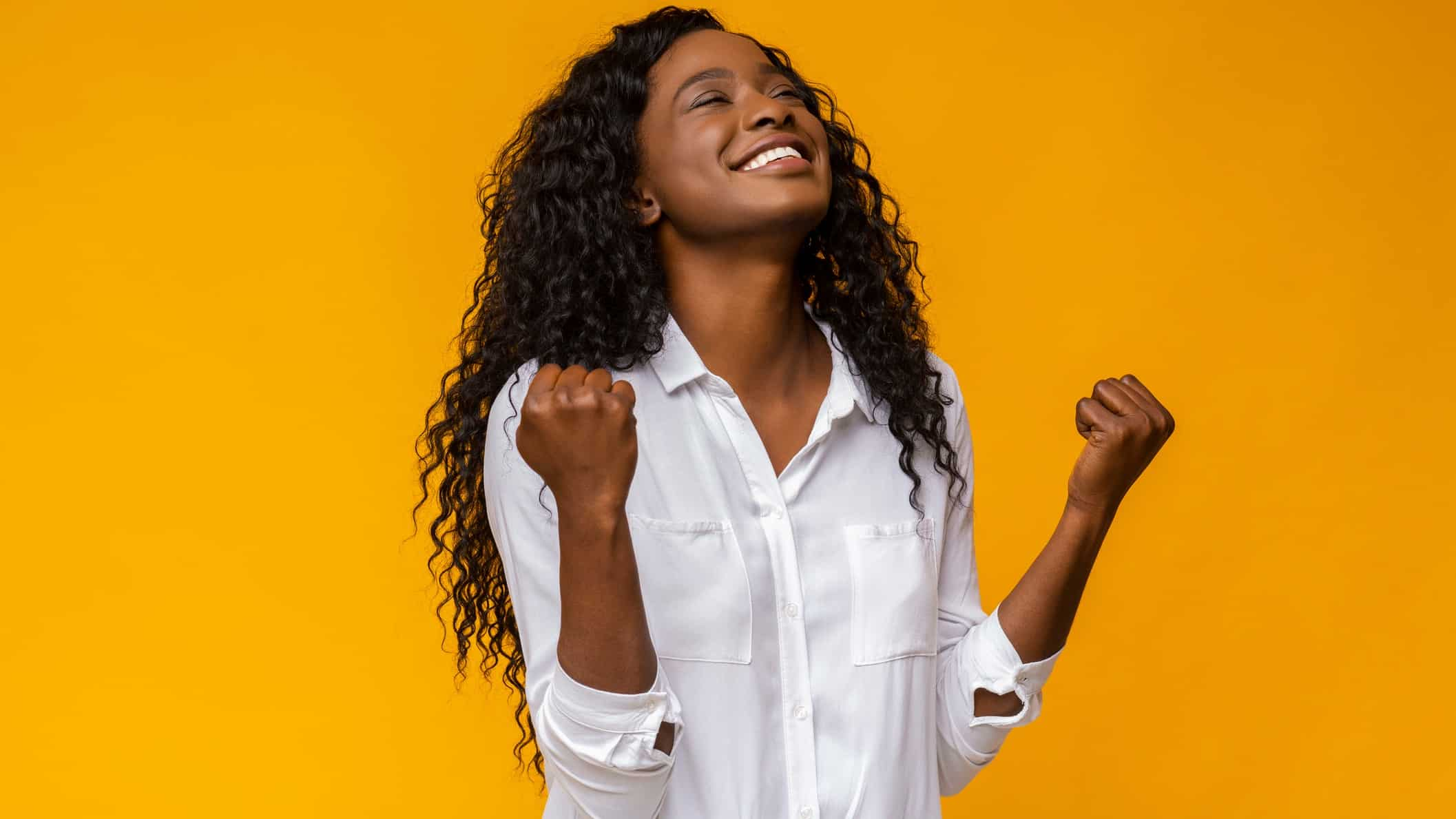 A happy woman raises her face in celebration, indicating positive share price movement on the ASX