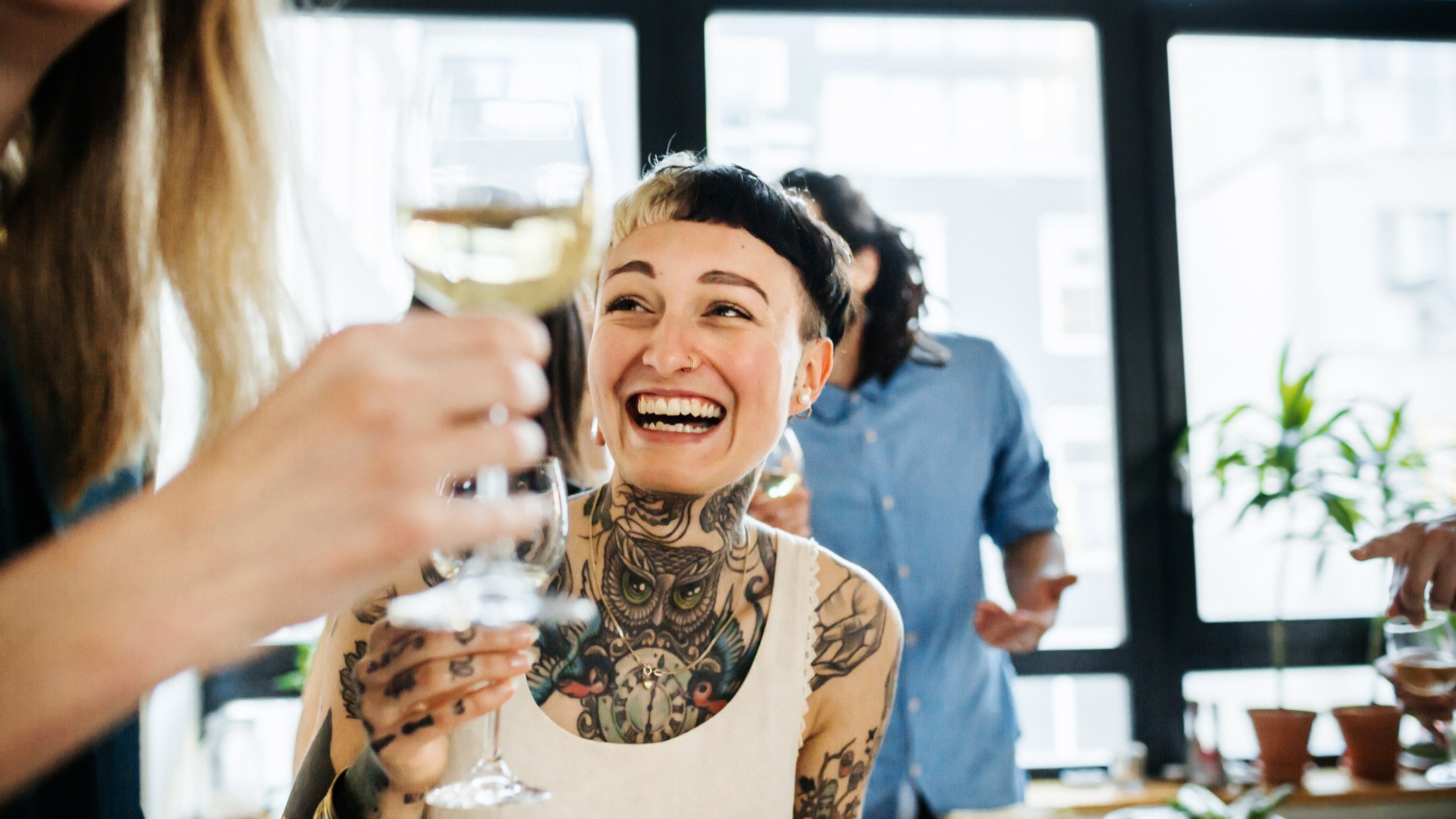 smiling person with tattoos enjoying a glass of wine with others