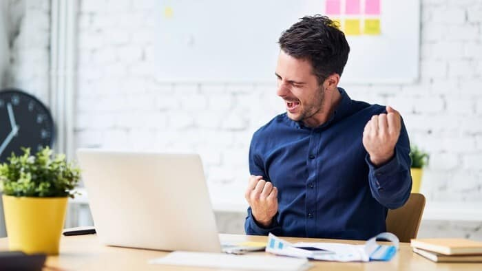 Happy investor punches air in front of laptop