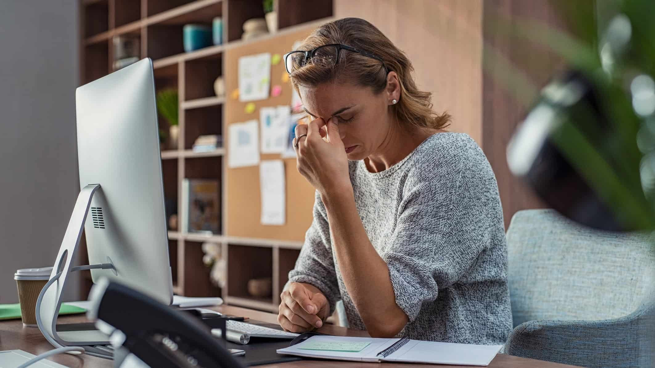 Female investor in front of computer with hands at forehead