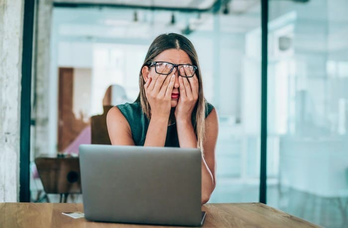 Investor covering eyes in front of laptop
