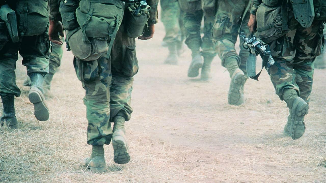 Line of military troops walking on dusty road