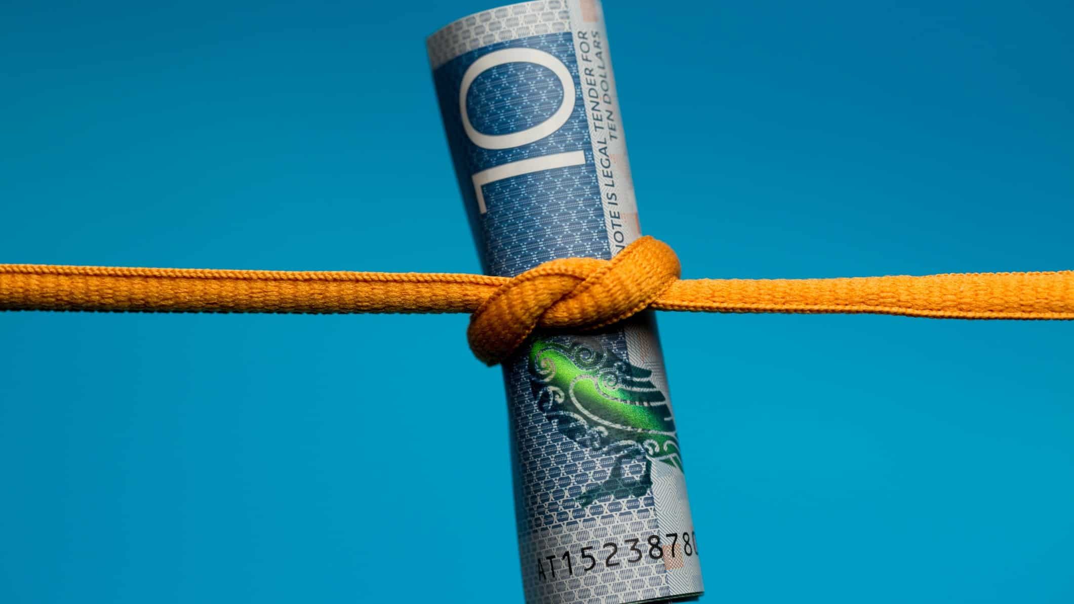 New Zealand $10 note being squeezed by an orange string to show recession