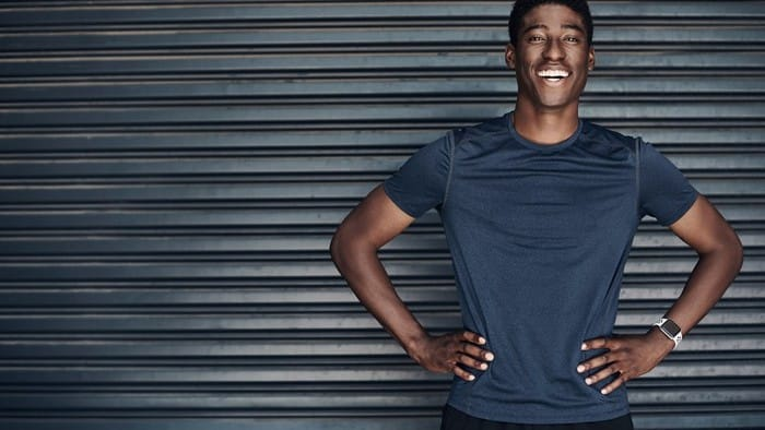 Man in activewear stands smiling in front of wall