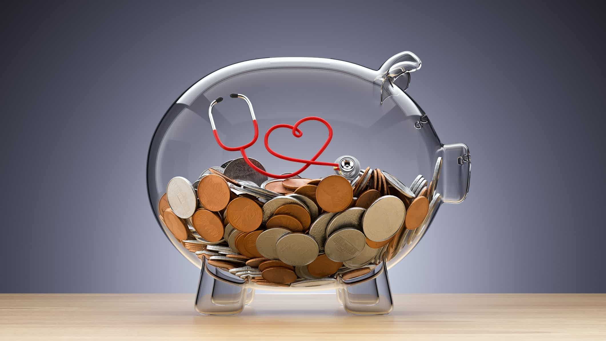 Glass piggy bank with coins and stethoscope in shape of a heart inside