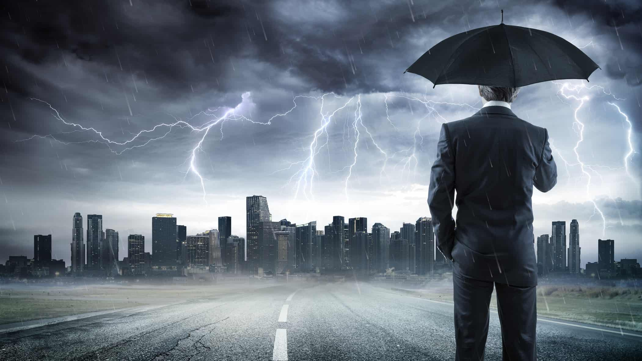 man holding umbrella looking at storm over city, recession, asx 200 shares