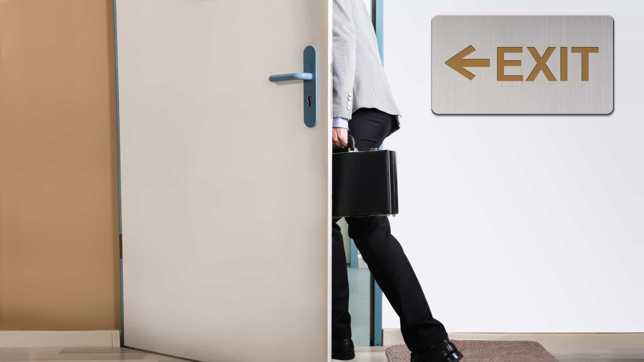 Businessman walks through exit door signalling resignation
