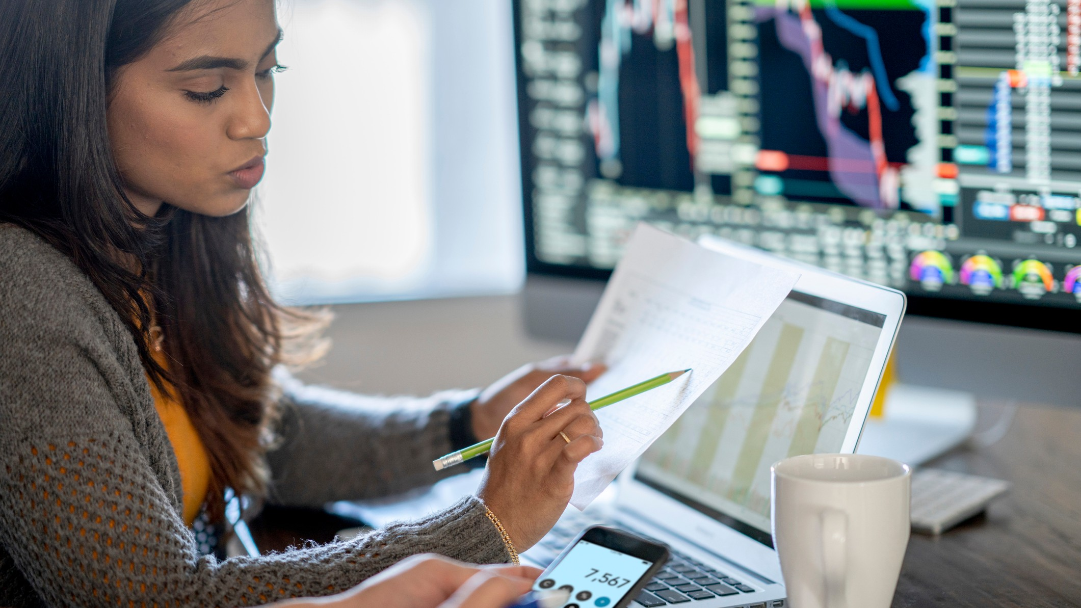 young woman reviewing financial reports at desk with multiple computer screens