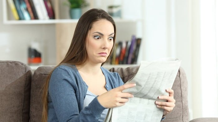 Woman sitting on couch holding newspaper with shocked expression on face