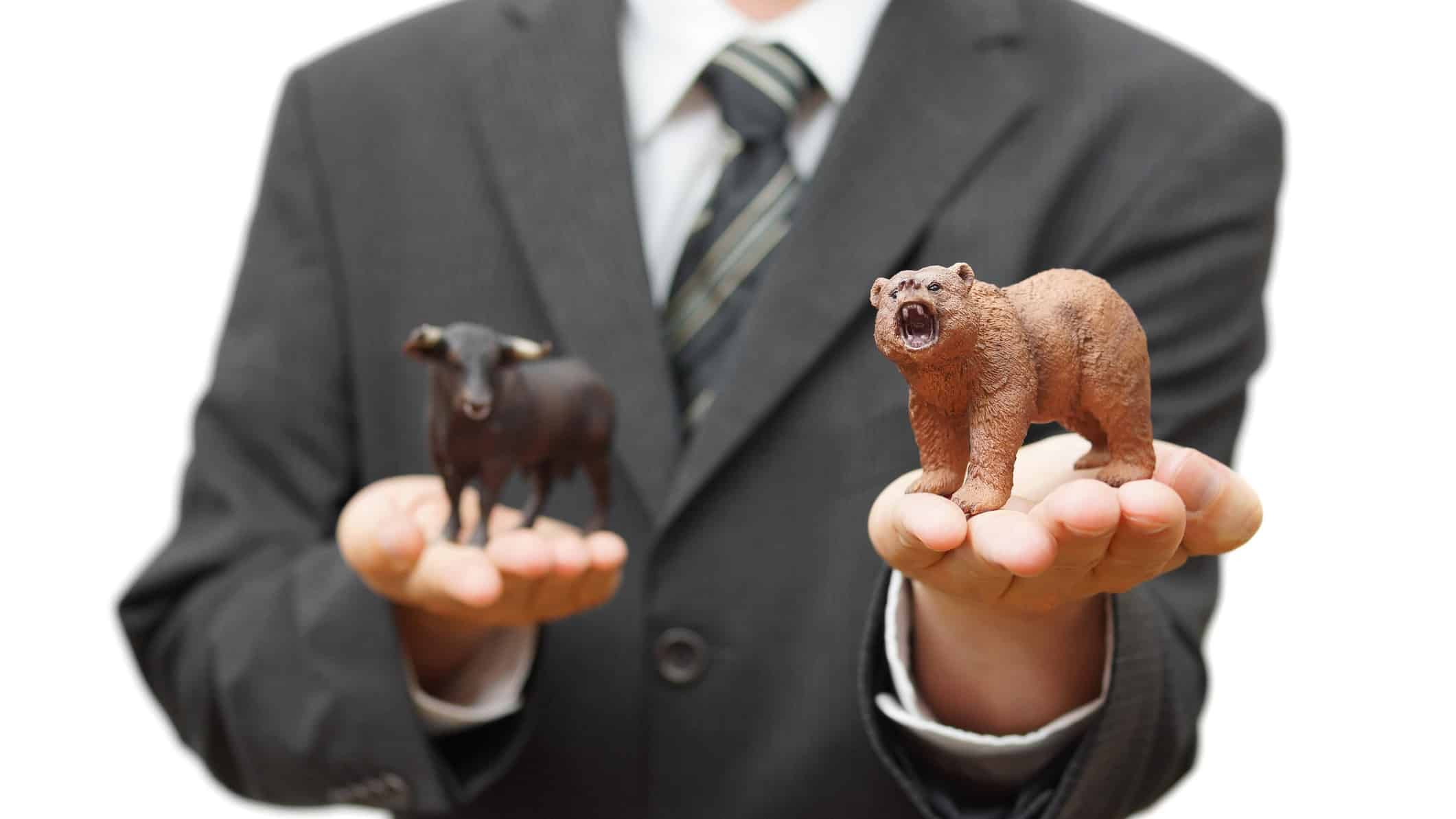 Businessman holding bear figurine in one palm and bull figurine in other