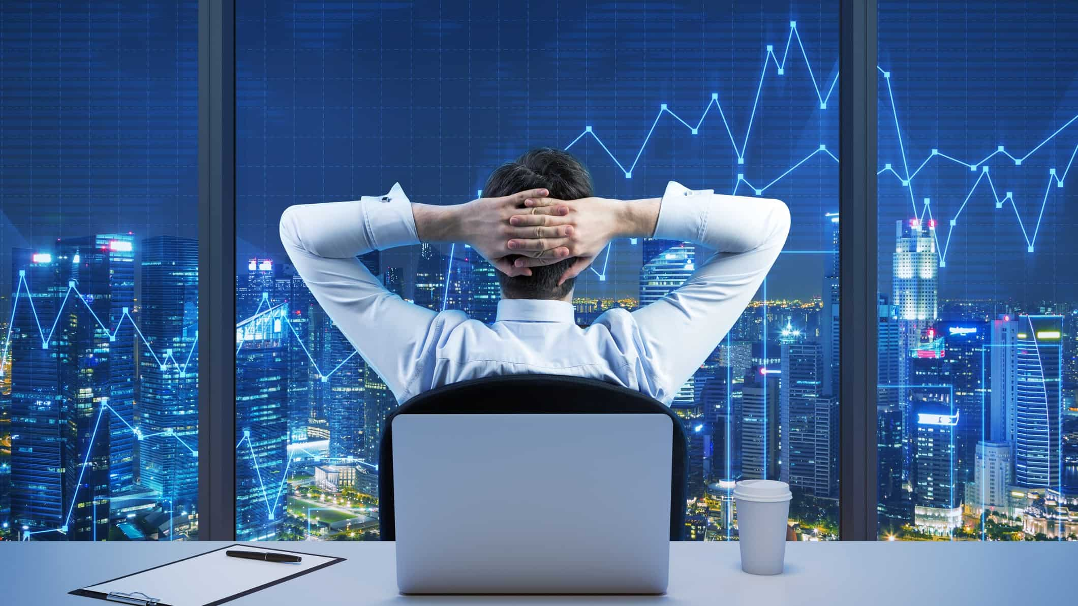 Business man at desk looking out window with his arms behind his head at a view of the city and stock trends overlay